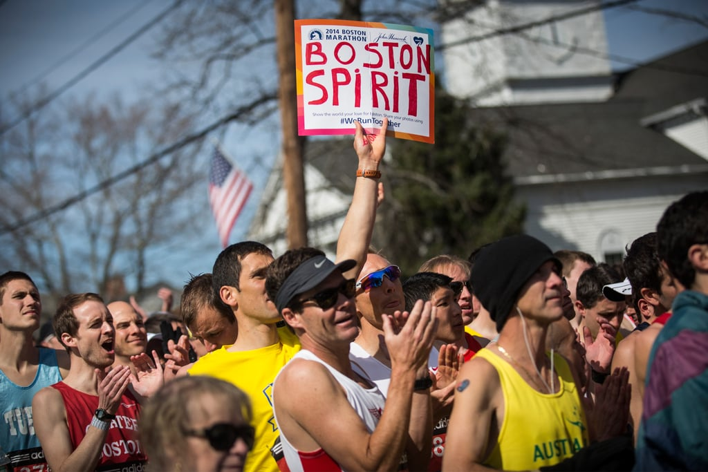 "Runners waited for the race to begin, with one participant holding up a ""Boston spirit"" sign."