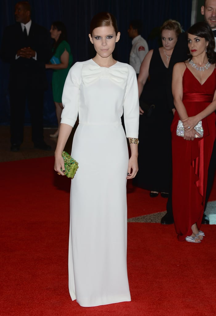 At the 2013 White House Correspondents' Dinner in Washington DC, Kate Mara was as ladylike as ever in her white Prada gown with an oversize bow at the neckline and a green jeweled clutch by the brand as an accent.