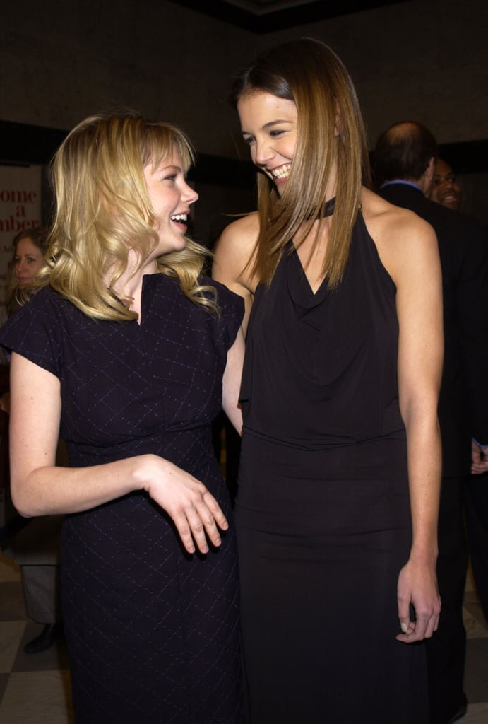 Katie Holmes and former Dawson's Creek costar Michelle Williams shared a laugh while celebrating the show's 100th episode in February 2002.