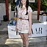 Katy Perry was the picture of festival style at the Harper's Bazaar pool party. She belted her floral top and white lace skirt, then added a bold cross necklace into the mix. Her black sunglasses, fedora, and black flat boots finished off the look.