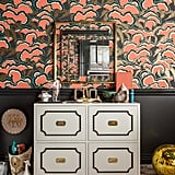 """""""I pushed the envelope and created a sense of theatrics and drama with the space by using layers of pattern and pops of color to energize and inspire,"""" says Tamara. She chose a five-color (including metallic gold) hand-screen-printed wallpaper from Portland-based Makelike called lush. The wallpaper, designed by Mary Kysar, uses water-based inks on recyclable paper. For the rest of the walls, Pratt & Lambert's Anthracite did the trick, using oil-based high gloss on the trim work and ceiling, and satin on the walls. The Nurseryworks Uptown Changer ($1,200), also designed by Tamara, easily transforms into bedroom or office storage, or even a dining room credenza once tots are out of diapers. Photos courtesy of: Marco Ricca"""