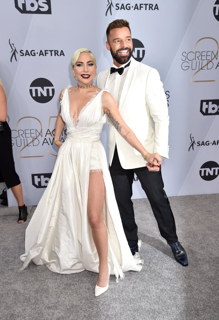 Now which NBC live musical is this? At the 2019 SAG Awards, Lady Gaga and Ricky Martin shared a delightful moment as they crossed paths on the red carpet. Instead of simply passing each other by, however, the two singers and actors managed to pose for photos that will be used to promote the musical that inevitably gets written about this very moment. Don't you love when two stars collide unexpectedly? Especially when they're not opposed to hamming it up for the camera? Yep, same. Though Gaga and Ricky have yet to actually work together, like many actors, they share a connection through Ryan Murphy: Gaga appeared in two seasons of American Horror Story, while Ricky appeared in American Crime Story: The Assassination of Gianni Versace, which has received several nominations throughout this award season. Here's hoping the universe — cough, Ryan Murphy — can bring these two together on a project in the near future.       Related:                                                                                                           Ever Wonder How Stars Are Born? Just Take a Look at Lady Gaga at the SAG Awards