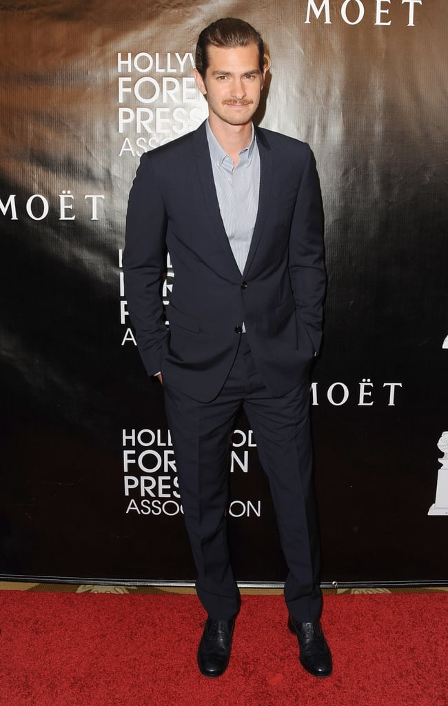 Andrew Garfield showed off a new look when he attended the Hollywood Foreign Press Association's annual grants banquet at the Beverly Wilshire Four Seasons in LA on Thursday. While the handsome actor rocked a beard this past Spring, he's now moved into mustache territory. The new facial hair may be for a role, but in any case, he looked dapper when he stepped out for the event this week, where John Krasinski also appeared with Emily Blunt and Topher Grace walked the red carpet with his fiancée. Keep reading for more pictures of Andrew Garfield's outing, then watch him in the 99 Homes trailer and enjoy some pictures of hot British actors hanging out together.