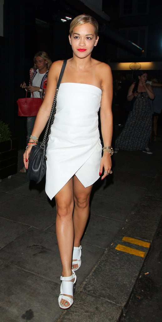 Rita Ora hit London Town looking undeniably polished in a white strapless dress with an asymmetrical hemline and chunky multistrap sandals.