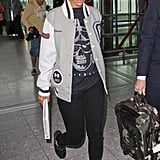 Rihanna takes a decidedly sporty take on the knit-hat trend, pairing the head warmer with a varsity jacket, a printed t-shirt, black skinny jeans, and high-tops.