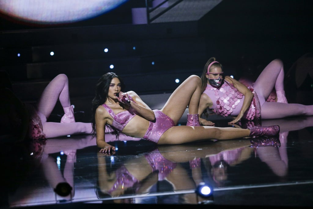 """Dua Lipa pulled out all the stops for her performance at the 2021 Grammys, stunning in not one, not two, but three head-to-toe custom pink outfits, courtesy of Versace. She first stepped on stage Sunday evening in a glittery magenta gown draped over a matching sequined bra top to perform """"Levitating"""" with DaBaby, and that look alone was a winner. With eye makeup, nails, and even her mic matching the Barbie-pink shade, she certainly committed to the concept.  Then, midperformance, she swapped the robe-like dress for an oversize lilac blazer with — you guessed it — flashy magenta boots to match. """"Making this blazer was no easy feat, and to be honest every outfit was so carefully and beautifully worked on,"""" Dua shared on her Instagram on Tuesday, crediting her stylist Lorenzo Posocco for the glamorous looks. She also offered a glimpse of the arduous process behind making the blazer, with involved each tiny sequin being individually attached to the jacket. """"People only see the final product but I see the process,"""" the singer added. For Dua's big grand finale, as she transitioned into her solo """"Don't Start Now"""" performance, she casually threw off the blazer to reveal her sexy sequined two-piece set — the perfect outfit for launching into her epic dance sequence. The singer, who was nominated for six Grammys this year, kept the pink theme going all night, starting off the evening in an ethereal Versace butterfly gown that truly sparkled from every angle. Ahead, check out Dua looking like the pop queen she is in her gorgeous Grammys performance looks.      Related:                                                                                                           The Stylish, Star-Studded Grammys Red Carpet Was Music to Our Ears"""