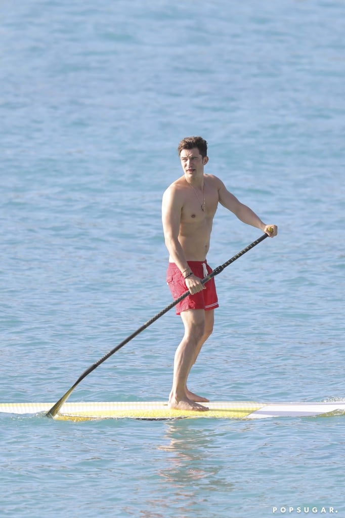 """Orlando Bloom was recently spotted hanging out at the beach in Malibu, CA, and has since moved on to St. Barts. On Monday, the actor put his impressive shirtless body on display while paddleboarding and relaxing on a yacht with a group of friends and a mystery woman. Unfortunately, he did keep his shorts on this time around, and he also appeared to be in good spirits, despite his split from girlfriend Katy Perry. While Orlando has yet to comment on the breakup, Katy addressed it via Twitter shortly after, urging """"a new way of thinking"""" and insisting that """"no one's a victim or a villain."""" She also opened up about her sexuality while speaking at the Human Rights Campaign Gala in LA over the weekend, saying she did more than just """"kiss a girl."""""""