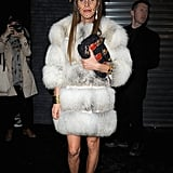Anna Dello Russo in a luxe fur coat, star halo headband, and black T-strap heels to the Versus Fall '12 show.