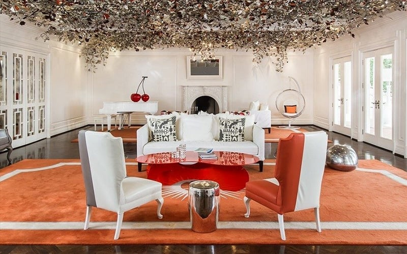 A whimsical floral art installation on the ceiling is a breathtaking addition to this white-and-tangerine living room.