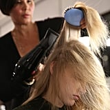 "To achieve the static effect, Gilbert blow-dried the hair upside down with Kérastase Mousse Substantive ($42) and a paddle brush by Mason Pearson. It's one technique that she even uses at home. ""If you dry your hair upside down then you get more volume because you lift your roots,"" she said. ""I love it because I have baby hair."""