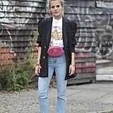 Could this be any more '90s? Not only is this stylish woman sporting light-washed, high-waisted jeans, but she is also wearing white sneakers, a blazer, and a fanny pack! It's like she stepped into all three of the Friends characters' closets and came out as their perfect style child.