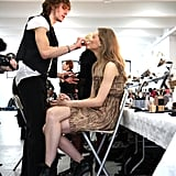 Model Lindsey Wixson chats as her makeup is applied backstage.