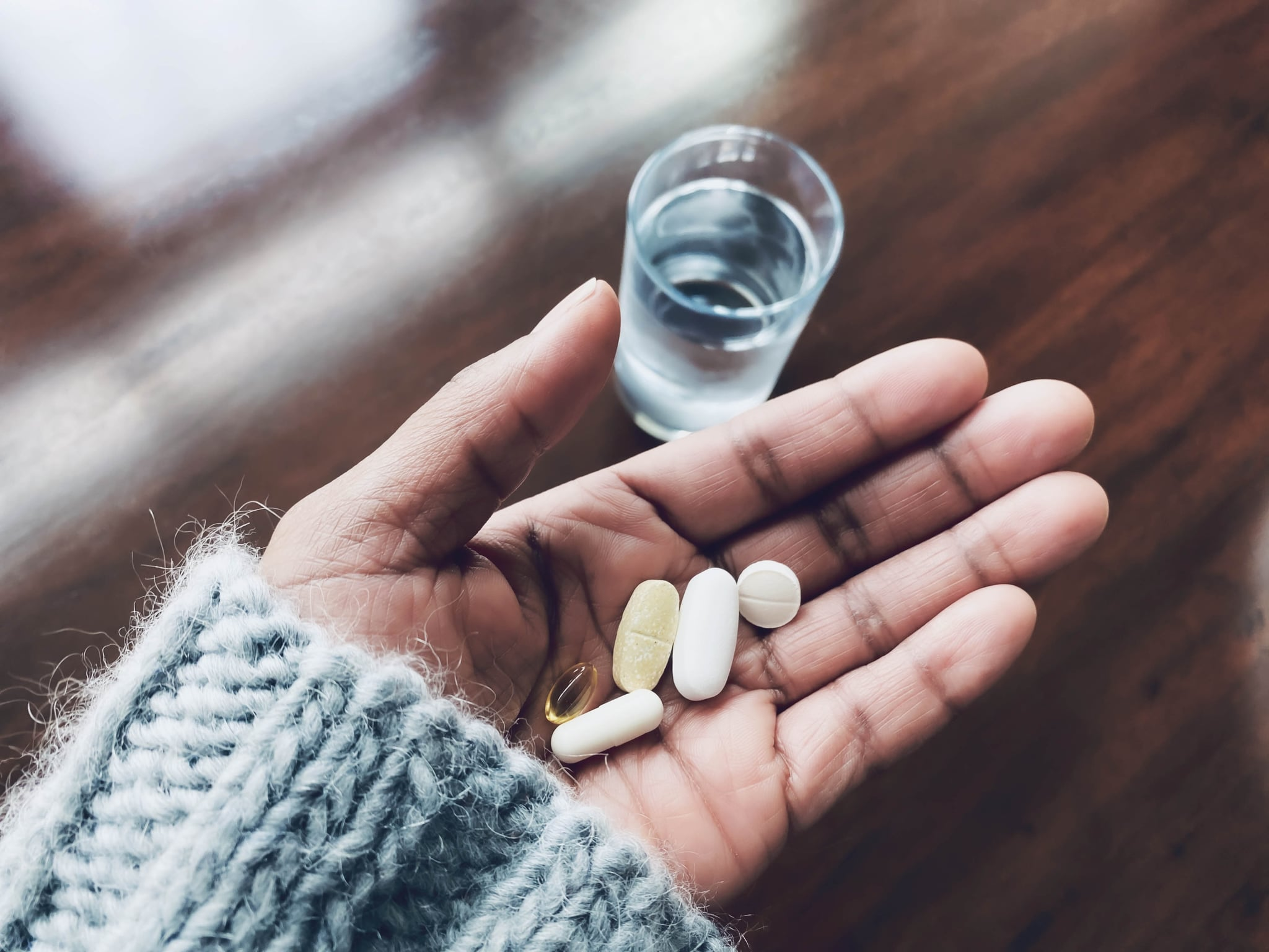 Close-up of woman's hand holding Vitamin C, Vitamin D, a probiotic and other nutritional supplements