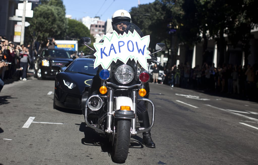 "A police officer escorted the Batmobile with a ""kapow"" sign on the front of his motorcycle."