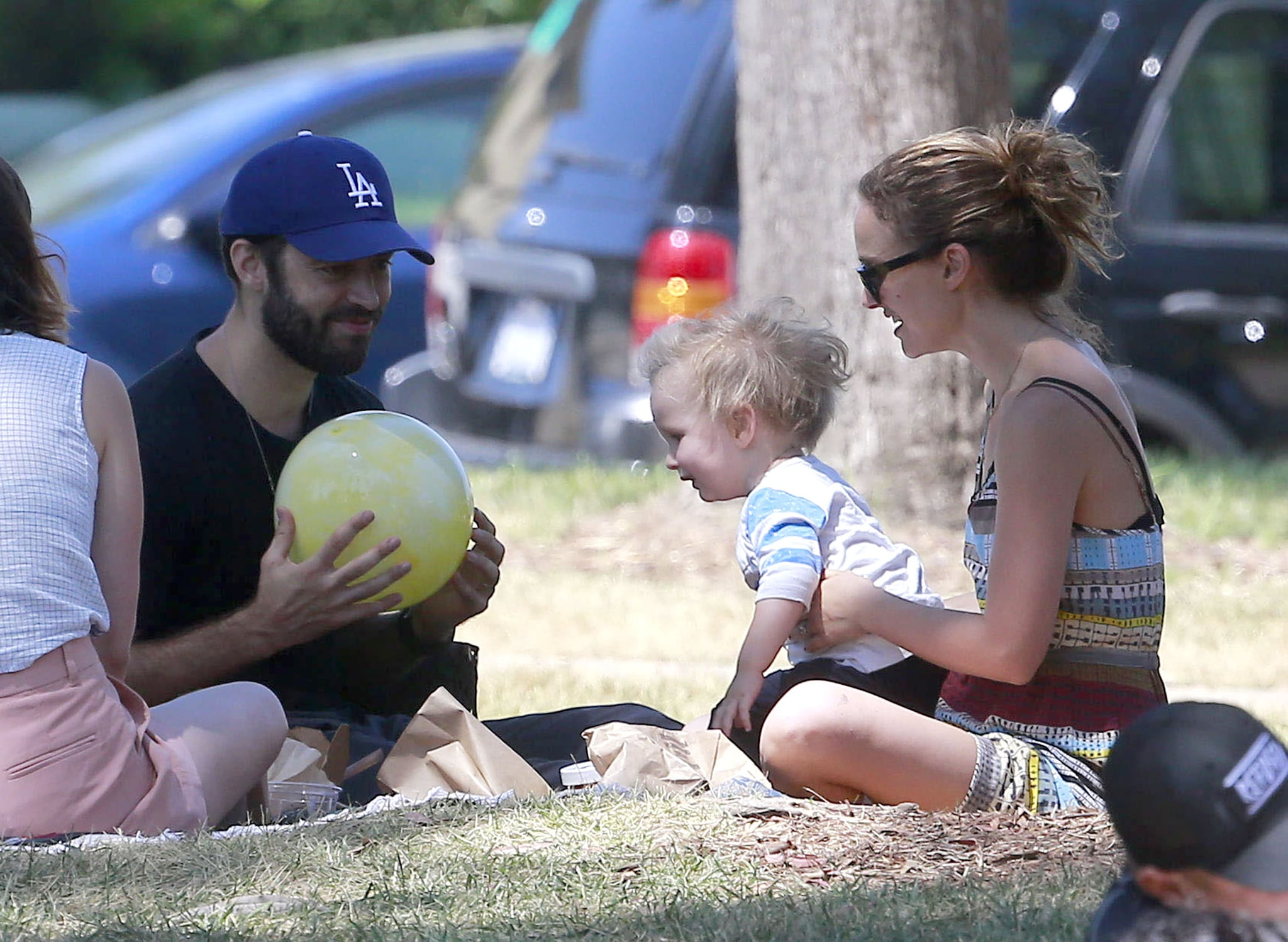 Benjamin Millepied and Natalie Portman played with their son in the grass.