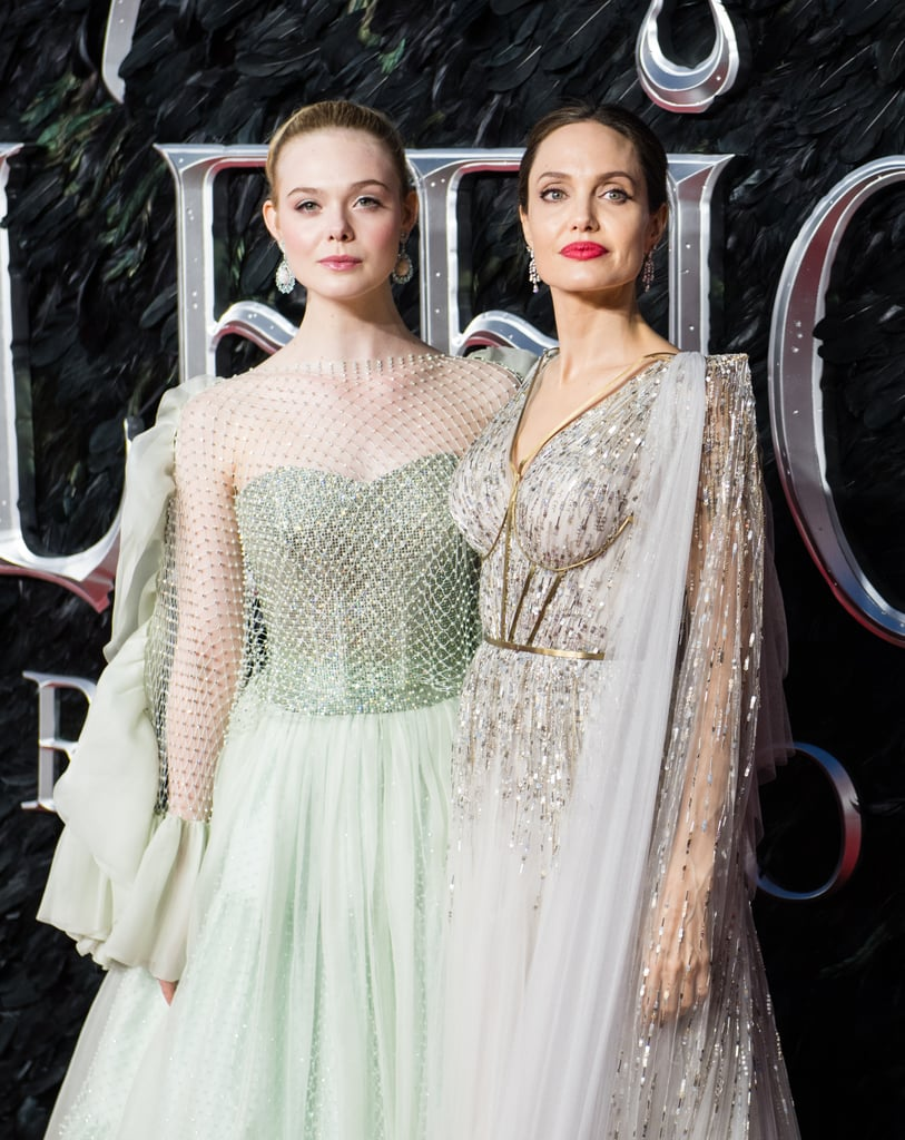 We knew the Maleficent: Mistress of Evil press tour was going to serve up some serious looks, and Angelina Jolie and Elle Fanning have definitely not disappointed. Angelina's given us plenty to swoon over, including a sexy strapless Versace gown, a flirty Ralph & Russo flapper dress, and a dramatic Givenchy top, but it looks like both she and her costar saved the best for London. Hitting the red carpet for the movie's premiere at the IMAX in Waterloo, both stars were truly stunning in embellished gowns. Angelina's pale silver dress came courtesy of British couture brand Ralph & Russo, and the custom design featured lavish beaded embellishment on layers of tulle, with a draped cape that framed her back tattoos perfectly, almost making them look like they were part of the gown. Gold cage detail on the front of the bodice gave the dress an armoured feel, which added a very Maleficent-esque toughness to the otherwise floaty and ethereal gown.       Related:                                                                                                           Angelina Jolie Looks So Regal in London, We Almost Confused Her With a British Royal               Speaking of ethereal, Elle Fanning was the perfect fairy princess in her mint green Armani Privé gown, which was customised especially for her and featured a jewelled mesh overlay with a ruffled trim — the perfect counterpart to Angelina's dramatic floor-length cape. Both looks were stunning and perfectly kept with the characters the actresses play in the movie. We're finding it difficult to decide which one we love the most. Keep reading to take a closer look at each gown from all angles for yourself, and see if you find it any easier to make a decision.