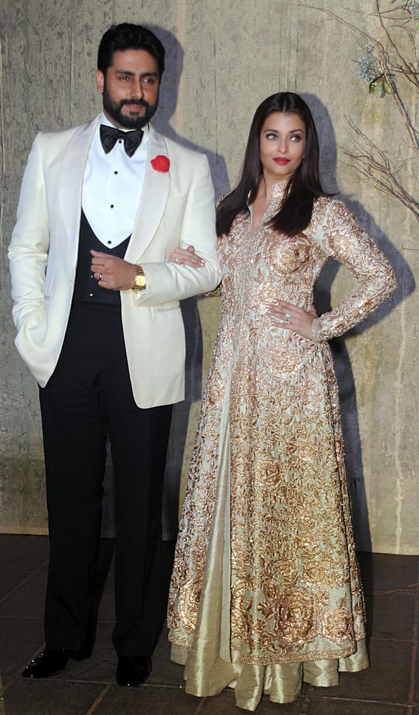 Posing with her husband Abhishek Bachchan wearing a gold embroidered Indian outfit.