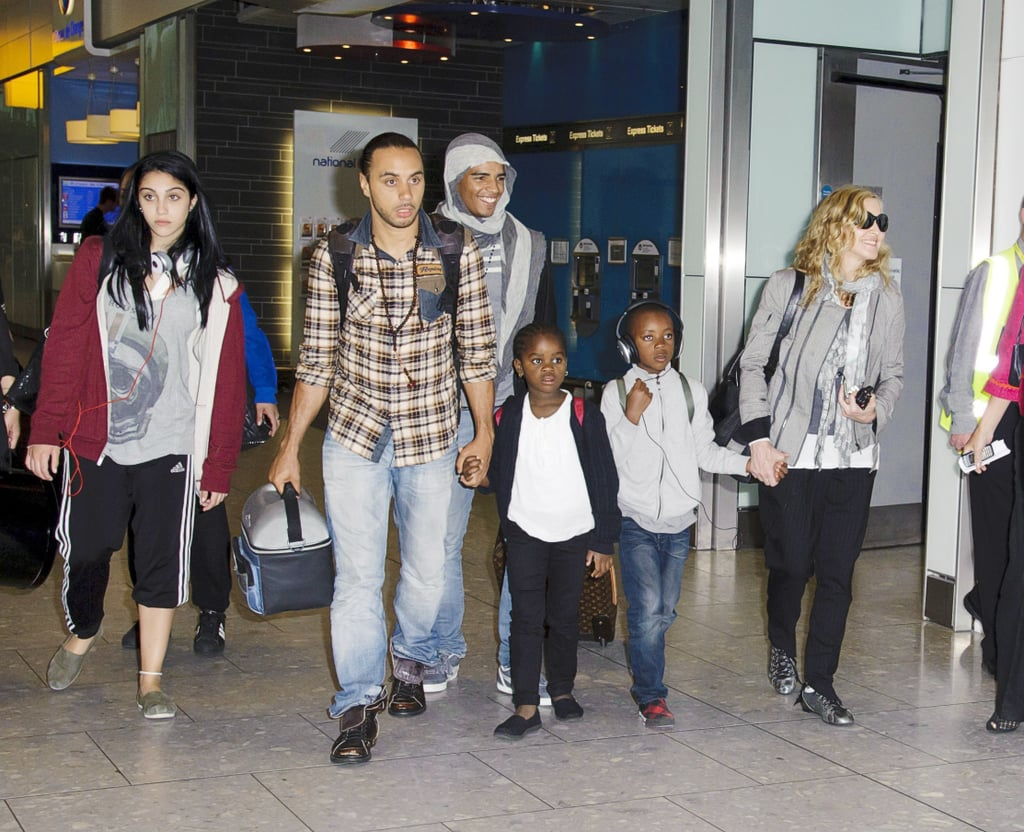 """Madonna touched down in London this morning with her kids, Rocco, David, Mercy, and Lourdes. Also in her entourage was her 24-year-old French dancer boyfriend, Brahim Zaibat, who spent the last few weeks in the US vacationing with Madonna. She, her children, and Brahim were at her place in the Hamptons, where they were pictured having a beach party a few days ago. Madonna and Brahim were seen kissing and hugging on the sand, apparently going strong despite rumors of a split a few months ago. There will be more celebrating in store today, as it's Madonna's 53rd birthday. We're celebrating by checking out Madonna's best beauty looks! Brahim will be by Madonna's side as she gears up for what will likely be a very busy end of 2011. Her directorial effort W.E., the story of King Edward VIII's romance with Wallis Simpson, will be out on Dec. 9. The film stars Abbie Cornish as Wallis, and the actress recently spoke about what it's like working with Madonna. Abbie said, """"You need to be totally switched on to the news and current affairs to talk to her – she asks you questions all the time and expects you to be up on everything that's going on, from Libya to the latest advances in technology. Her mind never stops working. She's also very funny. She tells a lot of good jokes. She is one of the coolest women on the planet."""""""