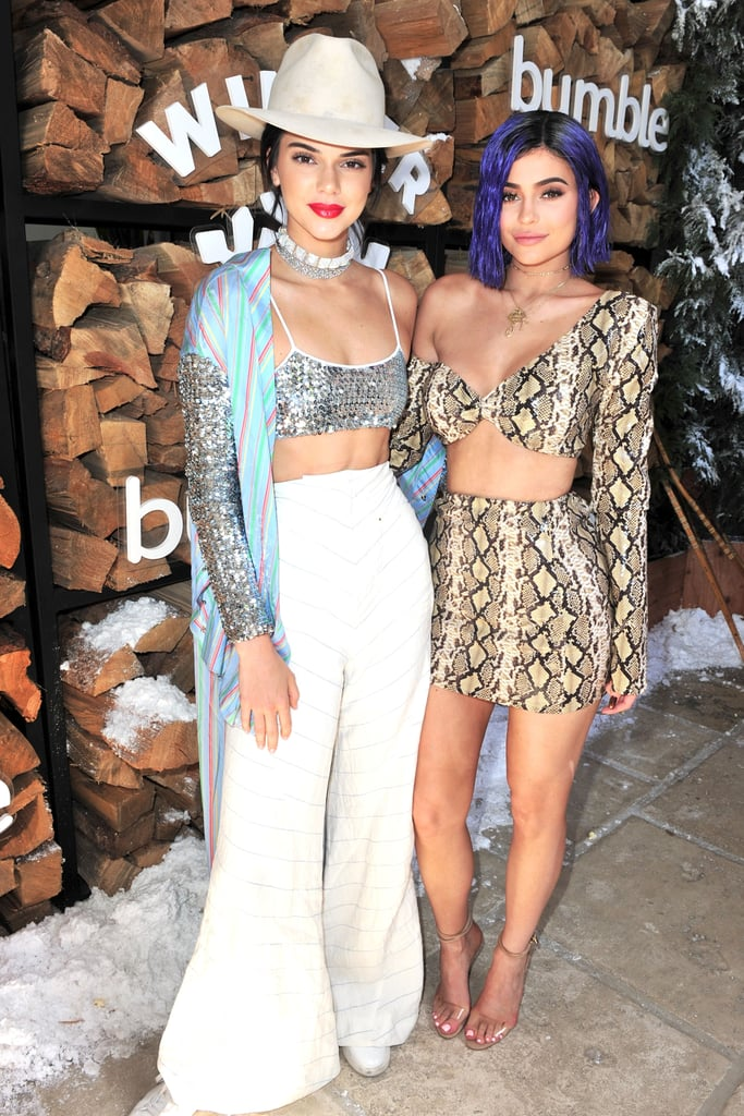 Kendall Jenner wearing a sequinned bra top, matching cardigan, and wide-leg trousers at the Winter Bumbleland, and Kylie wearing a snakeskin two-piece set.