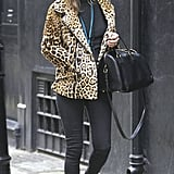 Behold, a quintessential Kate Moss look: a leopard coat with black skinny jeans, a Saint Laurent duffel, and black booties.