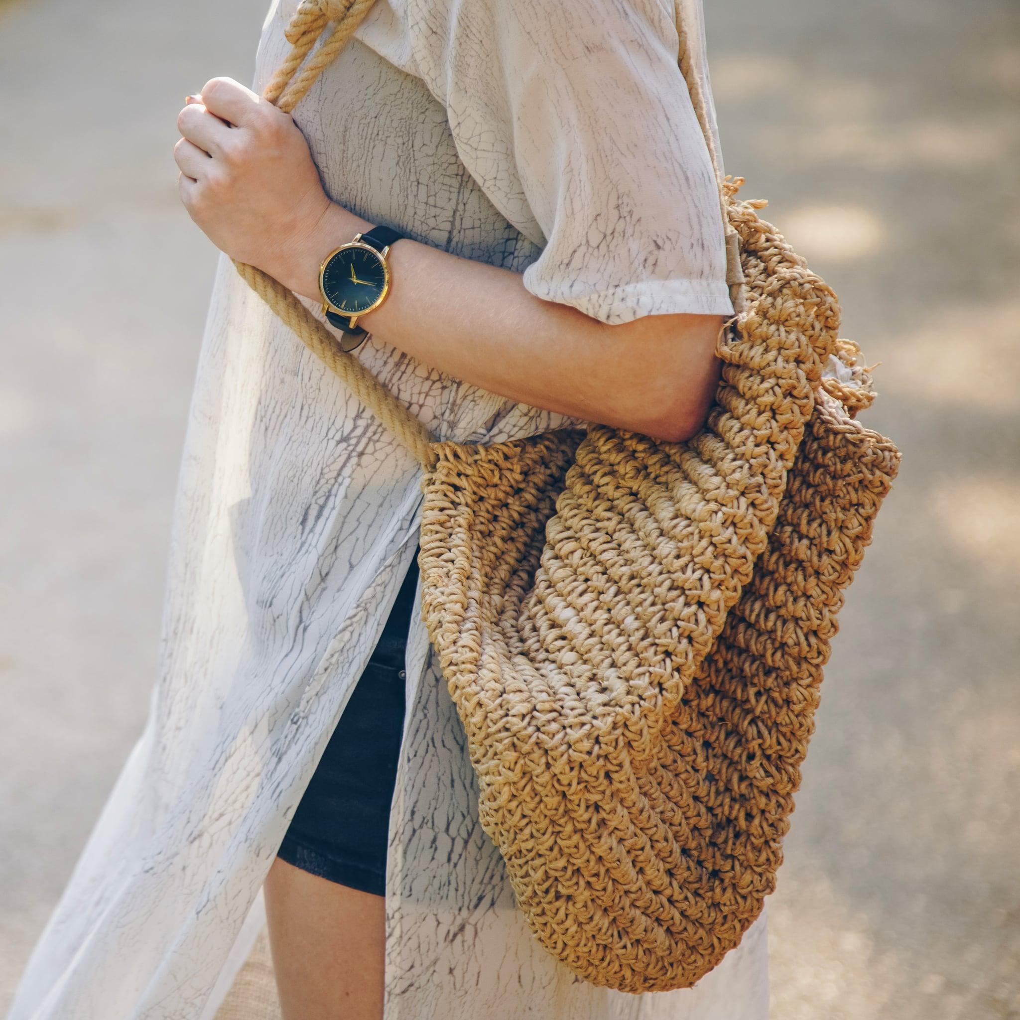 Close up of a stylish woman wearing a summer dress and holding a straw handbag while wearing a stylish wristwatch; Shutterstock ID 1243464847; Job: -