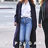 She styled a pair of button-up jeans with a crisp white blouse, a long sweater, and grandpa glasses.