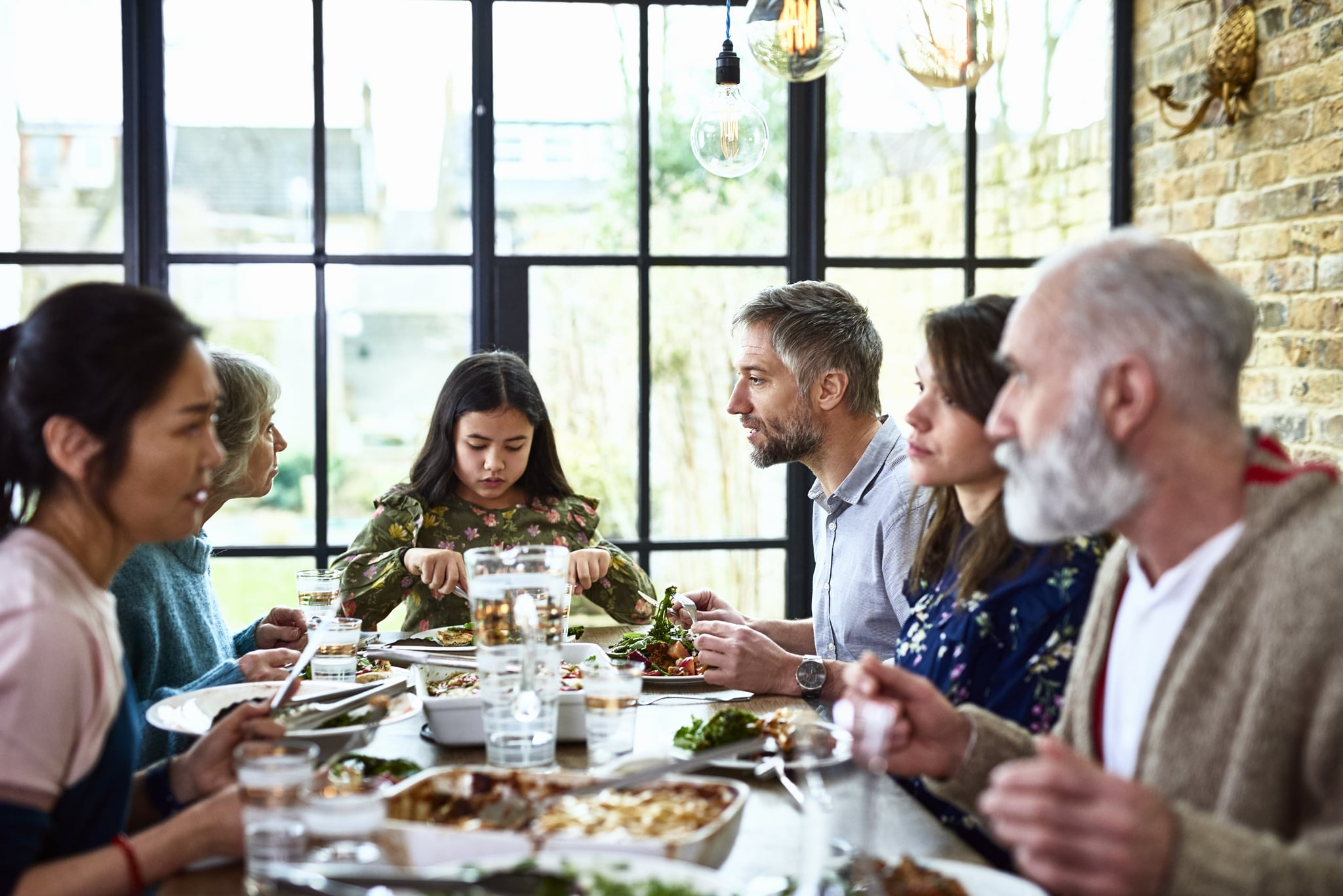 Social gathering between grandparents, adult offspring and pre teen granddaughter, sitting and eating dinner around dining room table, enjoying spending quality time over a leisurely meal, relaxed and friendly