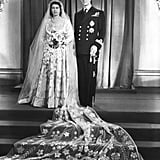 """The queen's wedding gown was inspired by a painting. In Botticelli's """"Primavera,"""" the central figure wears a silky, draped ivory dress affixed with rose blossoms. This is the inspiration designer Sir Norman Hartnell took for Elizabeth's elaborate confection. The gown had a 15-foot train and 10,000 pearls sourced from the United States.  Queen Elizabeth II saved ration cards to afford the fabric. Despite the gown's over-the-top inspiration, Elizabeth had to hoard her ration cards in order to purchase the material needed for her wedding dress, like any other woman at that time. The fabric she ended up with was created at Winterthur Silks Limited, with silk from Lullingstone Castle's Chinese silkworms.  All of her jewelry held sentimental value. The tiara she wore was one of her mother's, the diamond-encrusted Queen Mary Fringe, which was actually made for Queen Mary in 1919 from a diamond necklace given to her by Queen Victoria. Flowers were used sparingly as decorations. The tables at the reception were decorated with simple pink and white carnations donated by the British Carnation Society, since purse strings were tight after the war. Posies of myrtle and white heather from Balmoral were also given out as wedding favors.       Related:                                                                                                           Prepare to Lose It Over Another Season of the Crown's Incredible Costumes"""