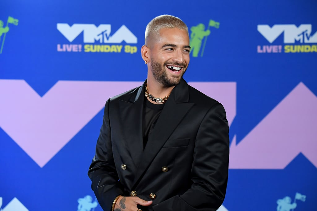 """It's easy to do a double take whenever Maluma's onscreen, but especially when he's serving spooky vampiric energy. The """"Hawái"""" singer channelled some serious Halloween vibes when he showed up to the 2020 MTV VMAs wearing silver fangs — Edward Cullen better watch out! We've seen an incredible amount of unique beauty looks from the show, but this one definitely took us by surprise.  It was already a big night for Maluma, who took home his first Moon Person for best Latin video, but his eye-catching accessory ensured his appearance would be unforgettable. Silver fangs aren't something you see every day, but hey, Maluma's guaranteed to have a costume come Oct. 31! Get a closer look at his vampy teeth ahead.       Related:                                                                                                           The MTV VMAs Red Carpet Was the Fashion Fix We've All Been Missing"""