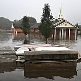 A casket floats in the water near a cemetery.