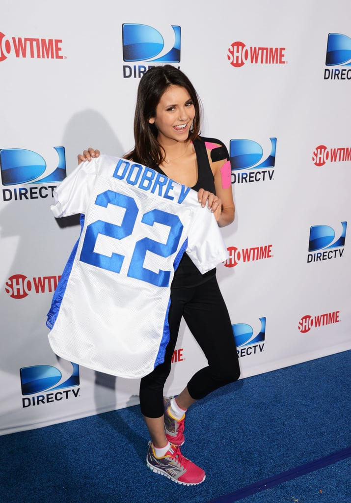 Nina Dobrev smiled with her jersey before heading in for another appearance at the celebrity bowl game at Super Bowl weekend 2013.