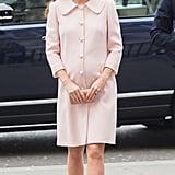 Wearing a pearl-adorned Alexander McQueen coat.