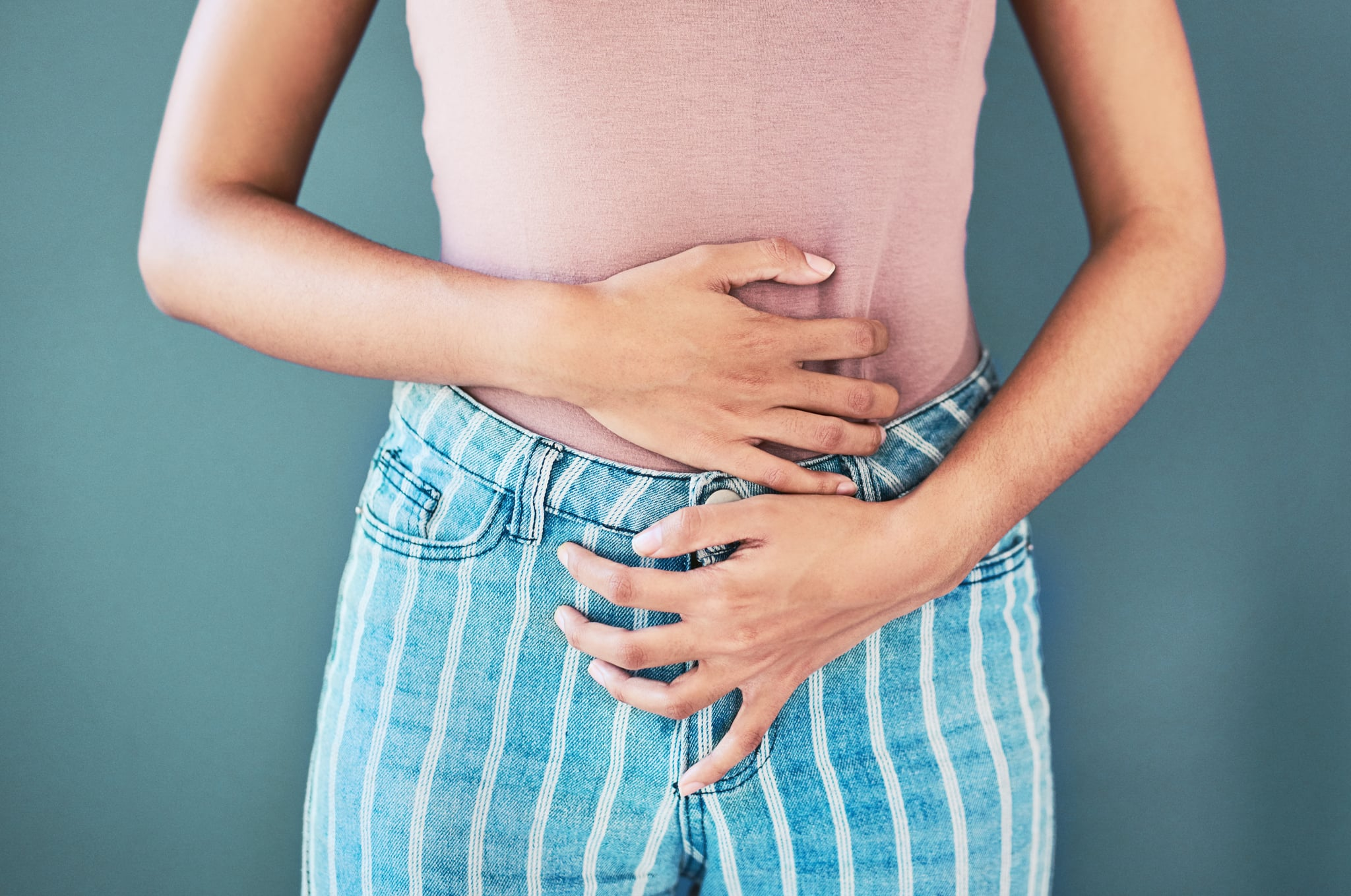 Shot of an unrecognisable woman holding her stomach in pain against a grey background