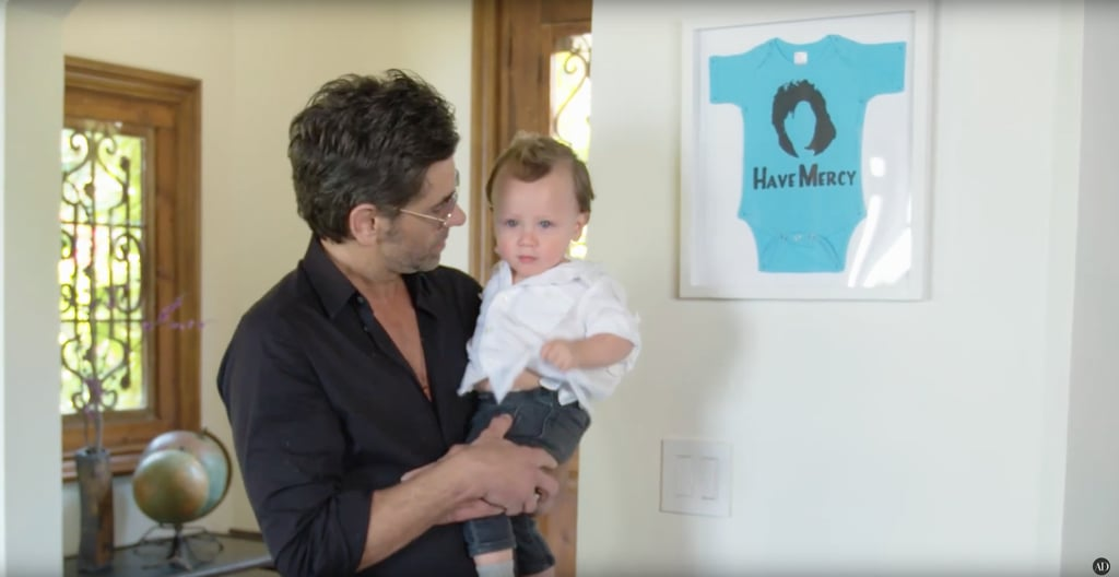 A blue onesie from his son's gender reveal is proudly displayed on the wall.