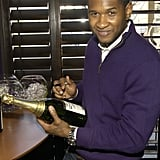 Usher signed bottles of Champagne during an Atlanta luncheon in December 2006.