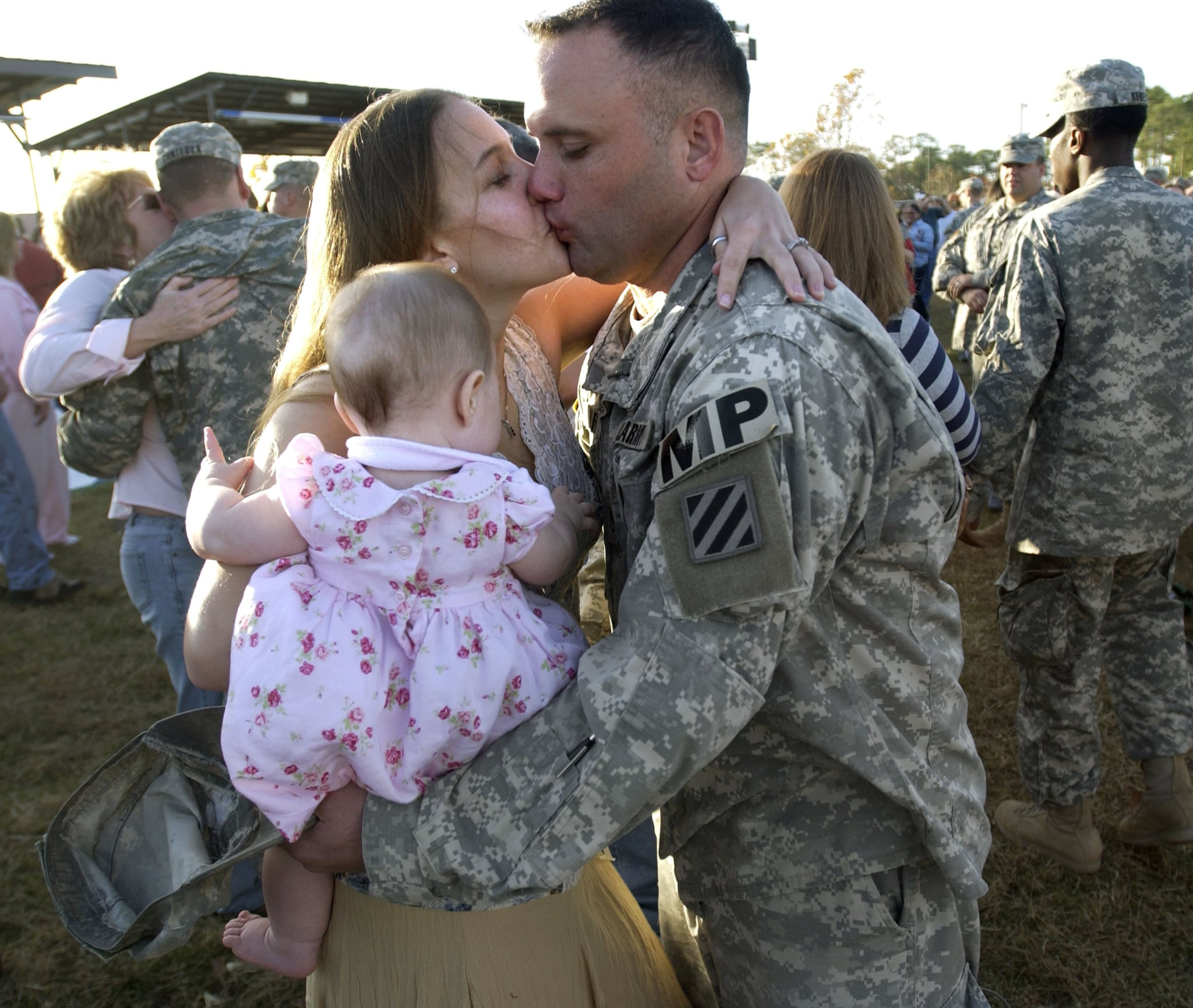 US Army Staff Sgt. Davis Wolfe kisses his wife, Kristine, and greets his 13-month-old daughter, Faith, in 2006.