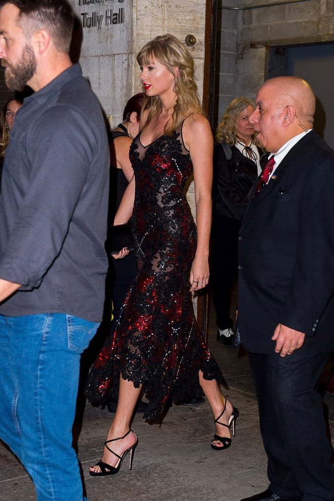 Taylor Swift has date night dressing down to a science. The 28-year-old singer recently stepped out to support boyfriend Joe Alwyn at the New York Film Festival premiere of his movie The Favourite, and she opted for a sultry gown that basically oozes glamour.  While Taylor and Joe have kept their romance relatively low-key, they don't shy away from style when they are seen in public together. Taylor's glittering, form-fitting black and red dress flared right above her ankles, given her a mermaid-like appearance. She paired the gown with strappy black heels, Eva Fehren jewelry, and carried a matching Christian Louboutin satin clutch. Her dashing English beau picked a sleek Dior suit with black dress shoes for their rare sighting — these two really make a picture-perfect couple. Keep reading to see more snaps of Taylor's sexy ensemble ahead, plus pics of her cute PDA with Joe.