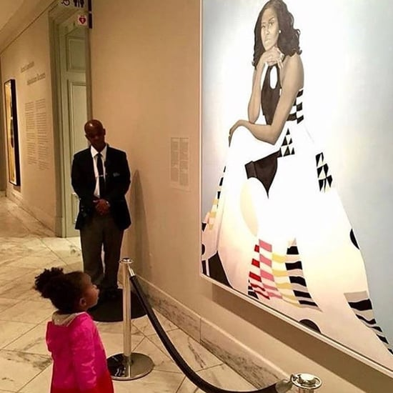 Little Girl Looking Up at Portrait of Michelle Obama