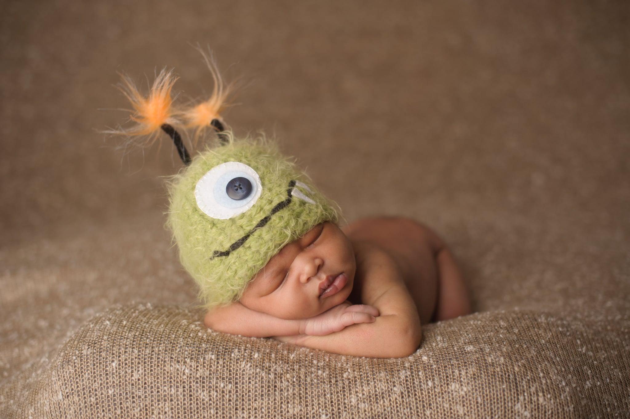 A newborn sleeping in a Halloween-themed monster hat.