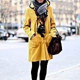 Street-chic perfection in a bold yellow coat — a camera was the ideal Fashion Week accessory.