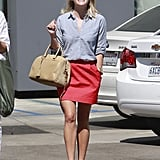 The left her salon looking fresh in a chambray shirt, coral skirt, and colorblock Pierre Hardy sandals.