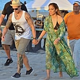 While shooting a music video on a beach in Fort Lauderdale, FL, Jennifer Lopez created a sexy pairing: a black triangle bikini topped with a green printed maxi dress.