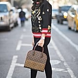 With an intricate sweater and metallic sneakers.