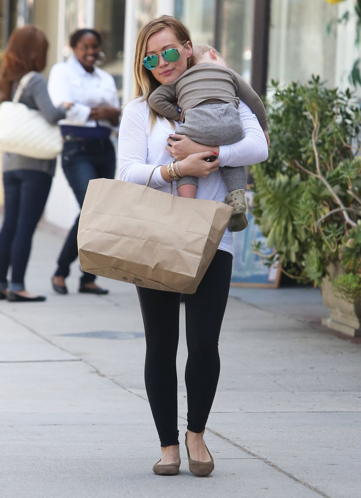 "Hilary Duff carried Luca, who rested his head on his mom's shoulder, in her arms as she ran errands around LA yesterday. She's been focusing much of her attention on her little man recently, especially since his exciting milestone. Luca turned 1 last week, and he celebrated by attending a Babies First Class in LA with Hilary. The proud mom was also sure to have a standout cake, which seemed to be a highlight of the festivities. Hilary shared a picture of the robot confection on her Twitter account, saying, ""Thank you Duff's cake mix for the coolest 1 year old's robot birthday cake ever! It was a big hit!"""