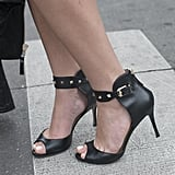 Gold studs amp up black peep-toe sandals.