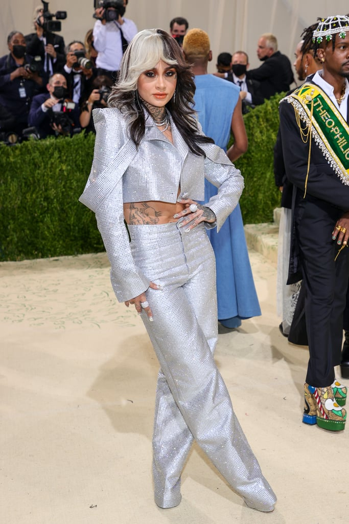 """This year's American-themed Met Gala delivered dozens of unforgettable celebrity fashion moments, thanks in part to the style wisdom of Law Roach. A full day after the Costume Institute Benefit, we can't take our eyes off the crystal-embellished Aliétte suit he styled for Kehlani. Sparkling from every angle, the suit included a cropped jacket with exaggerated shoulder pads and high-waisted, wide-leg pants that stretched all the way to the floor. Styled with feathered waves, silver platform boots, and a whole jewellery store's worth of diamond rings, the crystal suit made Kehlani look like a '70s disco queen.  A few hours later, the """"I Like Dat"""" singer hit up Rihanna's afterparty in a black pinstripe suit with flowers and symbols — including the words """"Come as You Are"""" — embroidered on the sleeves and Giuseppe Zanotti shoes. She paired the look with oversize hoop earrings and red heels that brought out the bright red roses clinging to her sleeves. Take in both of Kehlani's Met Gala-inspired outfits ahead, and check out Rihanna's diamonds on the red carpet here for even more bling.      Related:                                                                                                           Natalia Bryant Couldn't Sit Down at the Met Gala, but That Gorgeous Dress Makes It All Worth It"""