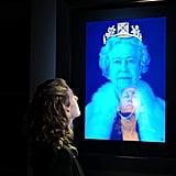 A woman looked at a 3D portrait of Queen Elizabeth with a jeweled diadem.
