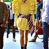 Wearing a ruffled yellow dress with a detailed belt.