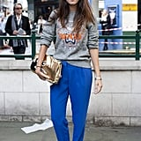 We love the dressed-up feel of this laid-back Kenzo sweatshirt outfit — her gold clutch, tapered blue trousers, and patent leather loafers punched up the low-key vibe tenfold.
