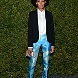 Solange Knowles made a chic arrival in a pair of Michael Kors cloud-print trousers, black blazer, white blouse, and standout accessories.